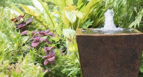 A fountain inside a cermic pot in a tropical garden